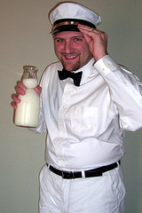 milkman-dressed-in-white-with-glass-bottle-of-milk