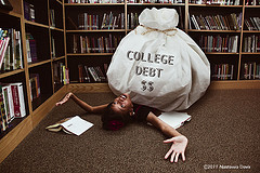 college-debt-for-student-with-big-bag-of-iou-holding-her-down