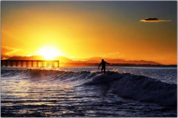 surfer-on-perfect-morning-out-on-water-sun-coming-up-bright
