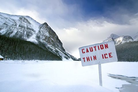 caution-thin-ice-sign-on-lake-within-mountains